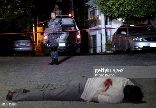 A police officer stands before the scene where a man was killed on a street in Acapulco Guerrero State Mexico on April 15 2016 Guerrero is one of...