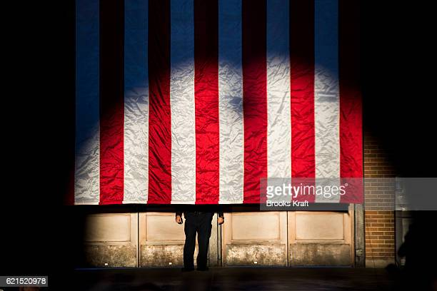 A police officer stands behind a flag while Democratic Presidential candidate Hillary Clinton attends a campaign rally in Eastern Market November 4...