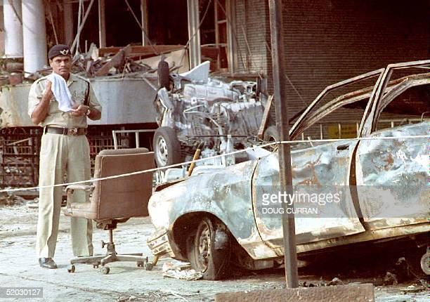 A police officer stands beside a charred automobile outside the Air India building 13 March 1993 one day after a series of bombs exploded in this...