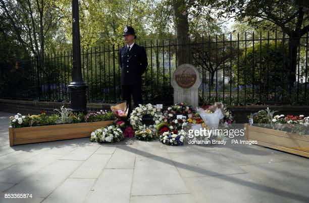 A police officer stands beside floral tributes during a memorial service held in St James Square London to mark the thirtieth anniversary of the...