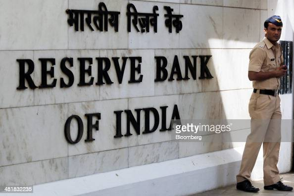 A police officer stands beside Reserve Bank of India signage at the central bank's headquarters in Mumbai India on Tuesday April 1 2014 Indias...