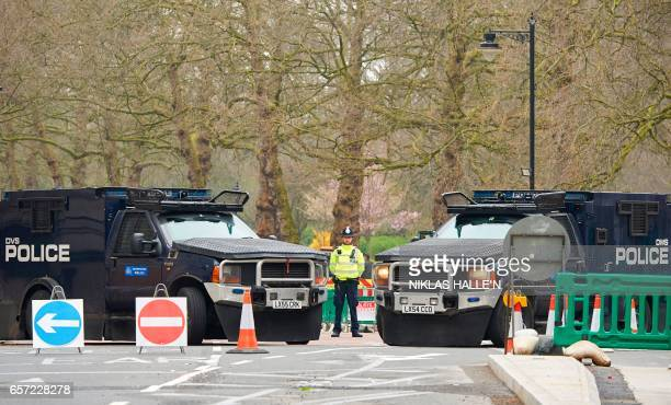 A police officer stands between armoured police personnel carriers on a street leading to the Houses of Parliament in central London on March 24 2017...