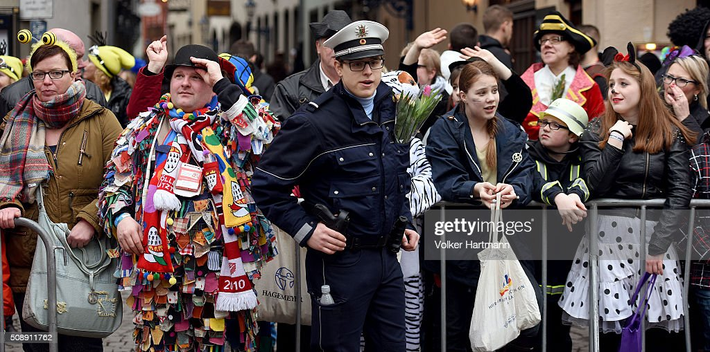 A Police officer stands between Carnival revellers during a carnival parade called 'Schull- un Veedelszoech' as part of the carnival season on February 7, 2016 in Cologne, Germany. Carnival partying and parades, a centuries-old tradition in western and southwestern Germany, traditionally occurs in February and runs until Ash Wednesday, the start of Lent, and culminates in Rose Monday parades and festivities. Police are on added alert this year, particularly in Cologne, due to the New Year`s Eve sex attacks on women that have been attributed to gangs of North African men, predominantly from Algeria and Morocco.
