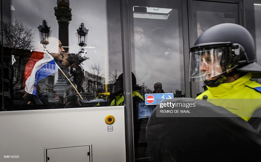 A police officer stands by as members of Pegida (Patriotic Europeans Against the Islamisation of the Occident) leave in a bus after holding a demonstration in central Amsterdam on February 6, 2016. Anti-Islamic group Pegida, which began as a movement in Germany in mid-2014 and has since spread to France and other European countries, has called on members and sympathisers across Europe to join marches on February 6. / AFP / ANP / Remko de Waal / Netherlands OUT