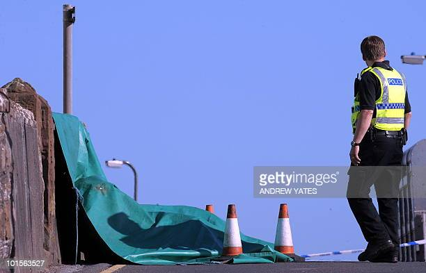 A police officer stands by the scene of a shooting in Seascale Cumbria north west England on June 2 2010 A gunman killed at least 12 people after...