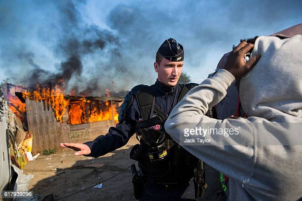A police officer stands guard after migrants burn down a shelter as authorities move in to clear the Jungle migrant camp on October 25 2016 in Calais...