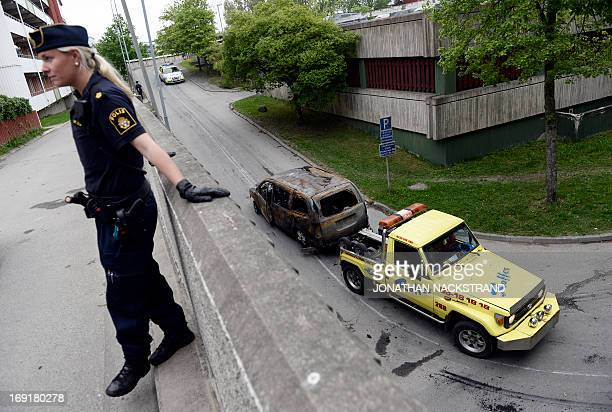 A Police officer stands guard as a burnedout van is towed away after youths rioted in Husby northern Stockholm on May 21 2013 Youths in the...