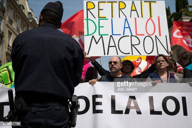 A police officer stands guard as a demonstrator holds a placard reading 'Withdrawal of Macron's law' during a protest organised by several unions...