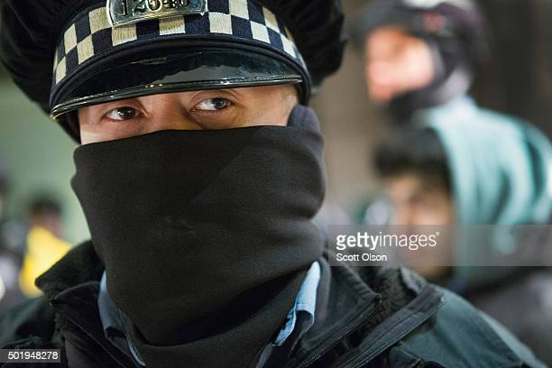 A police officer stands guard as a demonstrator who was participating in a march calling for the resignation of Chicago Mayor Rahm Emanuel is taken...