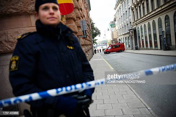 A police officer stands guard as a police and fire department team inspects a street and building where a suspicious package was found next to the...