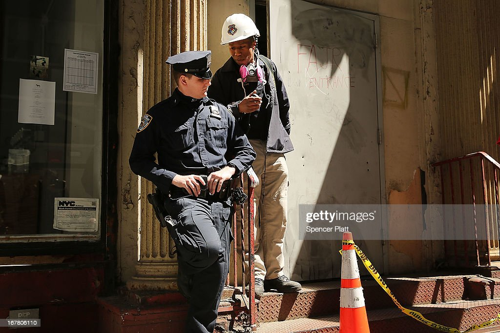 A police officer stands guard as a worker for the Medical Examiners office walks out of a building on Park Place in lower Manhattan where a piece of one of the planes destroyed in the September 11 attacks has been discovered on April 30, 2013 in New York City. The Medical Examiners office is searching the area for human remains.The part of the plane, a support structure from a trailing edge flap found on the wing of a Boeing 767, was discovered wedged between a mosque site and luxury high-rise apartment building, about three blocks north from the World Trade Center site.
