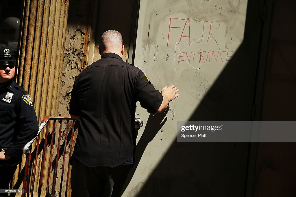 A police officer stands guard as a worker for the Medical Examiners office walks into a building on Park Place in lower Manhattan where a piece of one of the planes destroyed in the September 11 attacks has been discovered on April 30, 2013 in New York City. The Medical Examiners office is searching the area for human remains.The part of the plane, a support structure from a trailing edge flap found on the wing of a Boeing 767, was discovered wedged between a mosque site and luxury high-rise apartment building, about three blocks north from the World Trade Center site.
