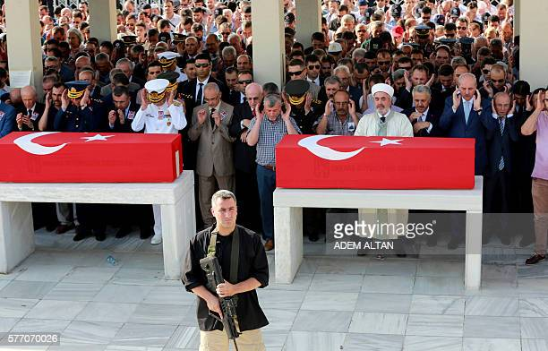 A Police officer stands guard as people pray during a funeral ceremony in Ankara on July 18 2016 for police officers killed during the failed July 15...