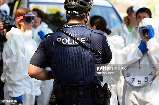 A police officer stands guard as protestors carry clocks to show timing is running out during an Ebola protest event in Brisbane on November 15 2014...
