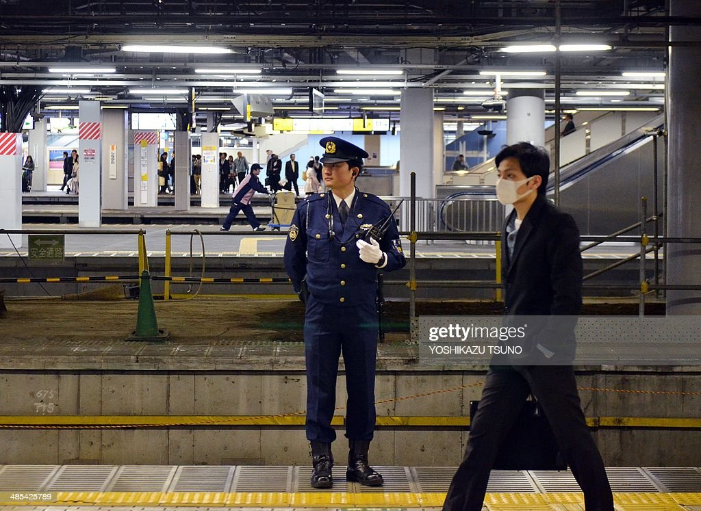 A police officer (C) stands guard at a train station in Tokyo on April 18, 2014 ahead of the upcoming visit of US President Barack Obama. The US leader will come to Tokyo for a three-day visit from April 23 for the first leg of his Asian tour. AFP PHOTO / Yoshikazu TSUNO