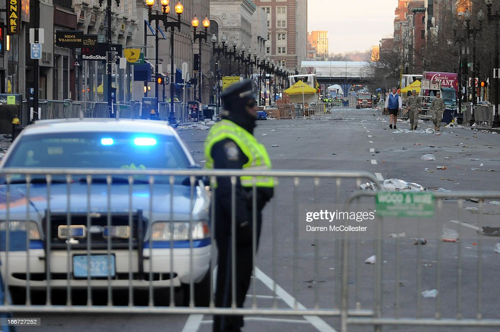 A police officer stands guard at the corner of Boylston and Arlington Streets with the marathon finish line bridge in the distance on April 16, 2013 in Boston, Massachusetts. Security is especially tight in the city of Boston after two explosions went off near the finish of the Marathon, killing three people and injuring at least 141 others.
