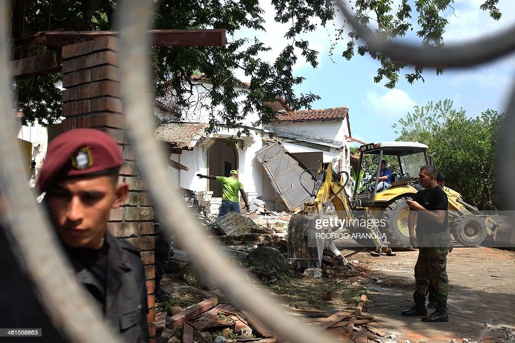 A police officer stands guard at the residence of Panama's former dictador Manuel Antonio Noriega, currently imprisoned in Panama, in Panama City, as it is being demolished on January 9, 2014 following a decision by the Health Ministry for considering it a breeding site of the Aedes mosquito that transmits dengue. Noriega, 79, who was extradited from France in 2011, is serving three 20-year prison terms for the disappearance of opposition activists during his years in power (1983-89). The former dictator has been petitioning to be placed under house arrest since 2012, arguing that his ailing health warrants it. Noriega was toppled from power in a US invasion in 1989, and spent nearly two decades in prison in the United States and France on drug charges. AFP PHOTO/ Rodrigo ARANGUA