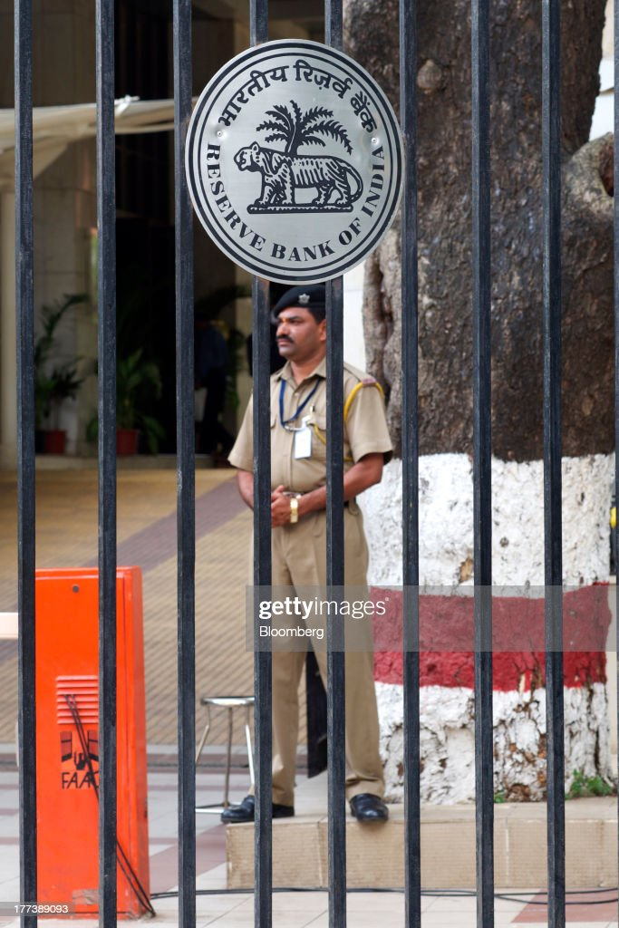 A police officer stands guard behind a gate at the Reserve Bank of India headquarters in Mumbai India on Friday Aug 23 2013 Indias rupee plunged 44...