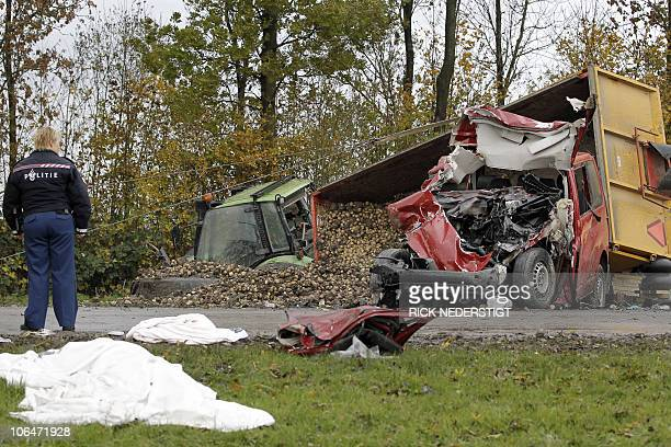 ADDITION A police officer stands guard by a corpse laying under a white sheet at the site of the collision between a coach and a tractor on November...