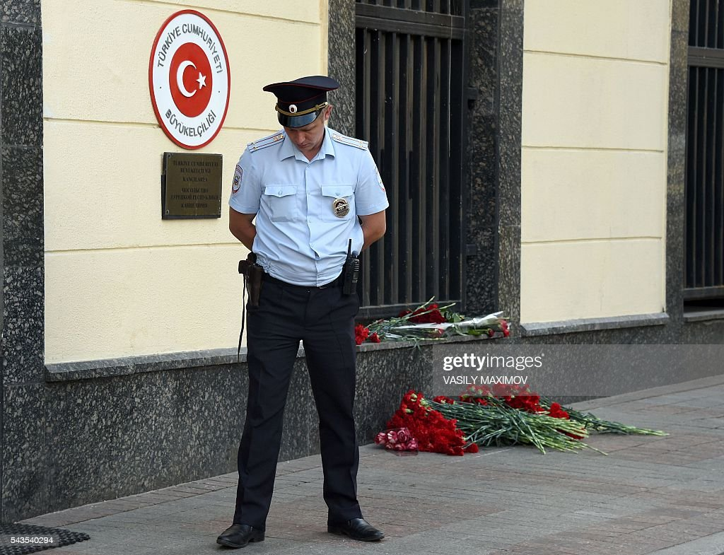 A police officer stands guard by floral tributes left outside the Turkish embassy for the victims of yesterday's suicide bombings at Istanbul's Ataturk airport, in Moscow on June 29, 2016. / AFP / VASILY