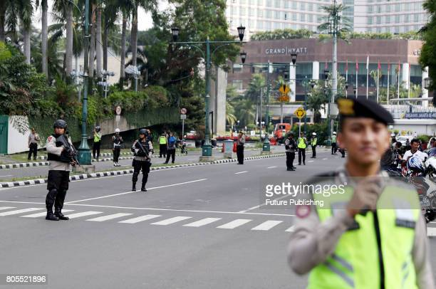 Police officer stands guard during convoy of vehicles carrying former US President Barack Obama and his family left the Mandarin Oriental Hotel to...