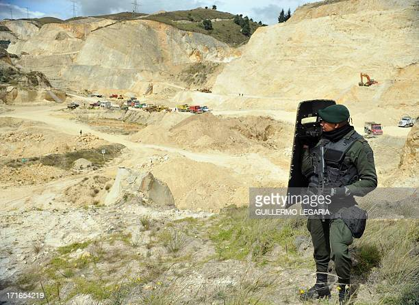 A police officer stands guard in a gravel sand and stone quarry in the municipality of Soacha outskirts of Bogota on June 27 2013 In a joint...