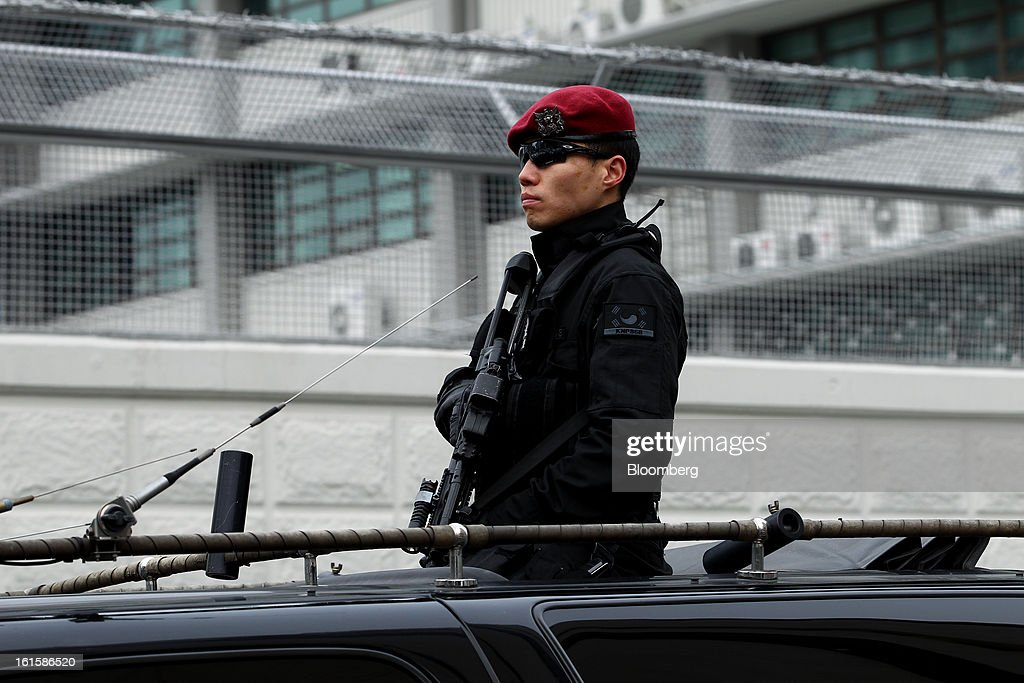 A police officer stands guard in a vehicle patroling around the U.S. Embassy in Seoul, South Korea, on Tuesday, Feb. 12, 2013. North Korea conducted its third underground nuclear test today, underscoring a disregard for an international community that has already isolated the totalitarian state from the global economy. Photographer: SeongJoon Cho/Bloomberg via Getty Images