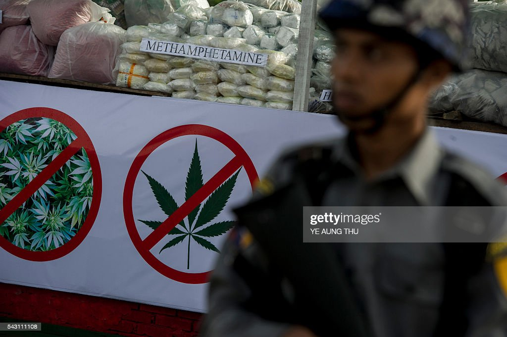 A police officer stands guard in front of seized drugs to be set on fire during a ceremony to mark the UN's 'International Day against Drug Abuse and Illicit Trafficking' in Yangon on June 26, 2016. Myanmar authorities on June 26 destroyed seized narcotics worth 56.31 million USD in anti-drug ceremonies in Yangon, Mandalay and Taunggyi. / AFP / YE