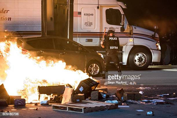 A police officer stands guard near a fire on the I85 during protests in the early hours of September 21 2016 in Charlotte North Carolina The protests...