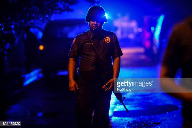 A police officer stands guard near the scene where a man was killed by unknown assailants in Quezon city Metro Manila Philippines July 15 2017 The...
