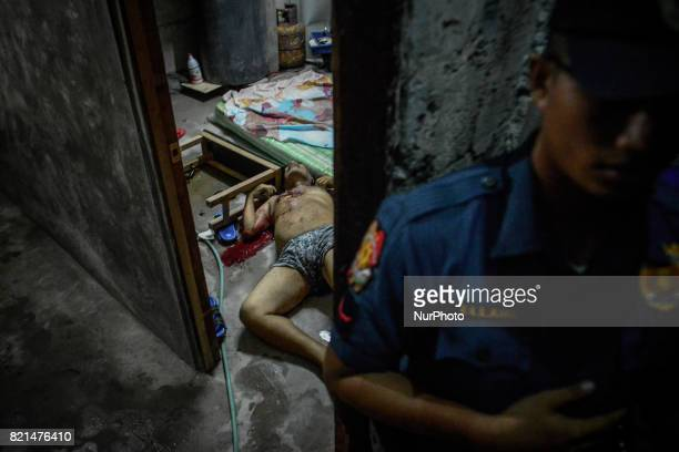 A police officer stands guard near the scene where a man was stabbed to death by an unknown assailant in Caloocan Metro Manila Philippines July 11...