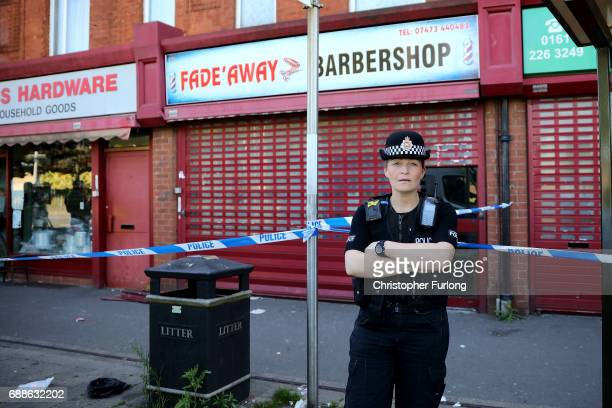 A police officer stands guard next to a barbers shop on Princess Road Moss Side after being raided by antiterror police during the investigation of...