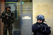A police officer stands guard next to a French soldier in the northern Paris suburb of SaintDenis city center on November 18 as French Police special...