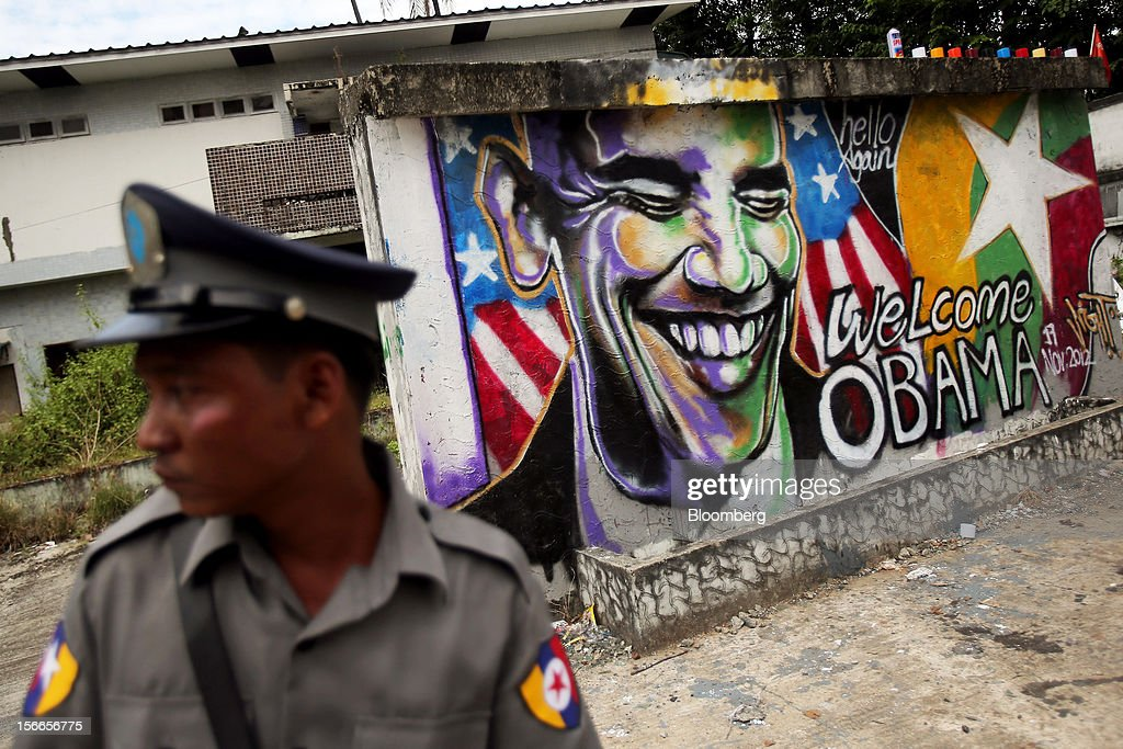 A police officer stands guard next to a graffiti by Burmese artist Arker Kyaw welcoming U.S. President <a gi-track='captionPersonalityLinkClicked' href=/galleries/search?phrase=Barack+Obama&family=editorial&specificpeople=203260 ng-click='$event.stopPropagation()'>Barack Obama</a> to Myanmar on a wall in Yangon, Myanmar, on Sunday, Nov. 18, 2012. President <a gi-track='captionPersonalityLinkClicked' href=/galleries/search?phrase=Barack+Obama&family=editorial&specificpeople=203260 ng-click='$event.stopPropagation()'>Barack Obama</a> will become the first sitting U.S. president to visit Myanmar when he travels to Yangon on Nov. 19 to meet President Thein Sein and Aung San Suu Kyi, the opposition leader who spent more than 15 years under house arrest before the country shifted to democracy after decades of military rule. Photographer: Dario Pignatelli/Bloomberg via Getty Images
