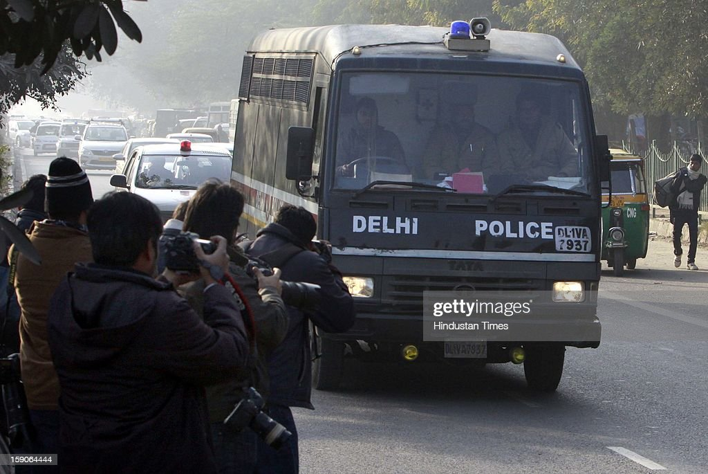 A police officer stands guard next to a police van believed to carrying the five men accused in a gang rape as they arrive at the Saket district court on January 7, 2013 in New Delhi, India. The men, who were set to appear in court are accused of a gang rape of a 23 year old girl who later died. The incident has caused outrage across India, sparking protests and demands for tough new rape laws and led to setting of special fast track courts for such incident.