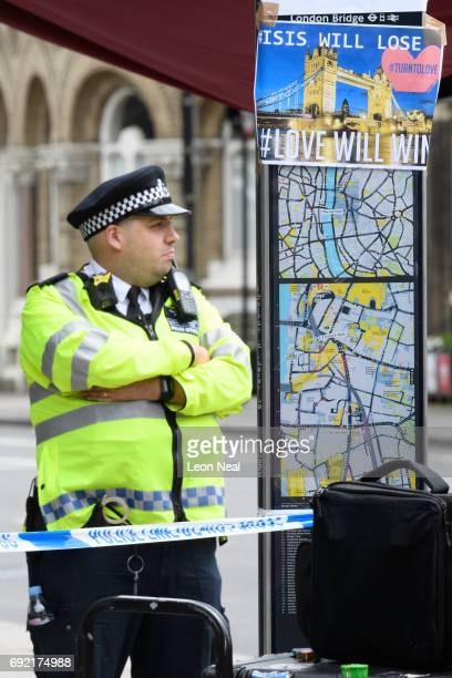 A police officer stands guard next to a sign reading 'ISIS Will Lose Love Will Win' following last night's London terror attack on June 4 2017 in...