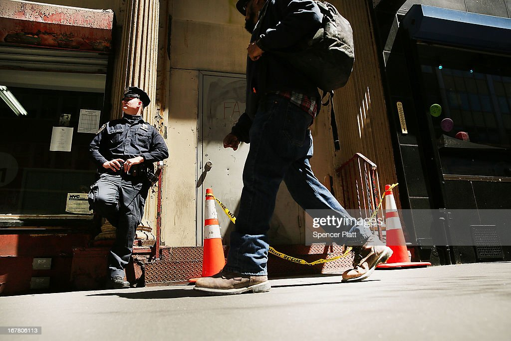 A police officer stands guard of a building on Park Place in lower Manhattan where a piece of one of the planes destroyed in the September 11 attacks has been discovered on April 30, 2013 in New York City. The Medical Examiners office is searching the area for human remains.The part of the plane, a support structure from a trailing edge flap found on the wing of a Boeing 767, was discovered wedged between a mosque site and luxury high-rise apartment building, about three blocks north from the World Trade Center site.