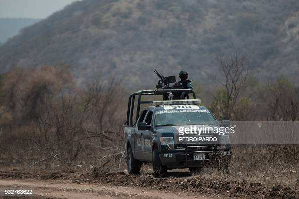A police officer stands guard on May 19 2016 next to a cordonedoff area near the small town of El Mirador alongside a road linking the Mexican towns...
