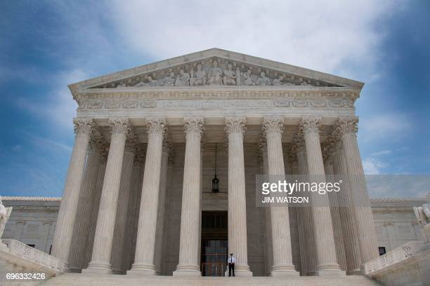 A police officer stands guard on the steps of the US Supreme Court in Washington DC June 15 2017 / AFP PHOTO / JIM WATSON