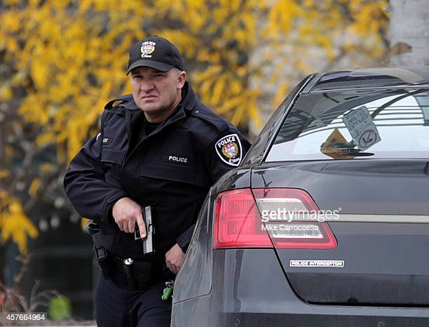 A police officer stands guard on Wellington St in downtown October 22 2014 in Ottawa Canada Officials are investigating multiple reports of shootings...