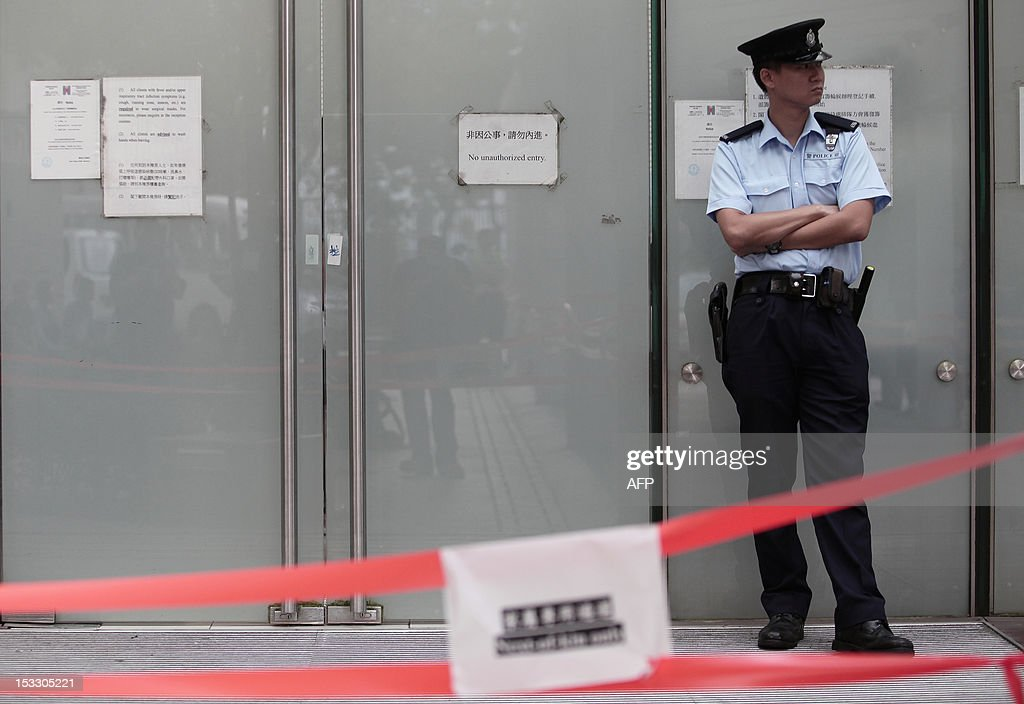 A police officer stands guard outside a cordoned off entrance to a public mortuary prior to relatives arriving to identify the dead bodies of their loved ones in Hong Kong on October 3, 2012, two days after a ferry collided with a pleasure boat killing at least 38 people a short distance from Lamma island. More than 120 passengers and crew were on the Hong Kong Electric company's Lamma IV to watch a huge National Day fireworks display in Victoria Harbour when the accident occurred just off Lamma, an island to the southwest of Hong Kong.