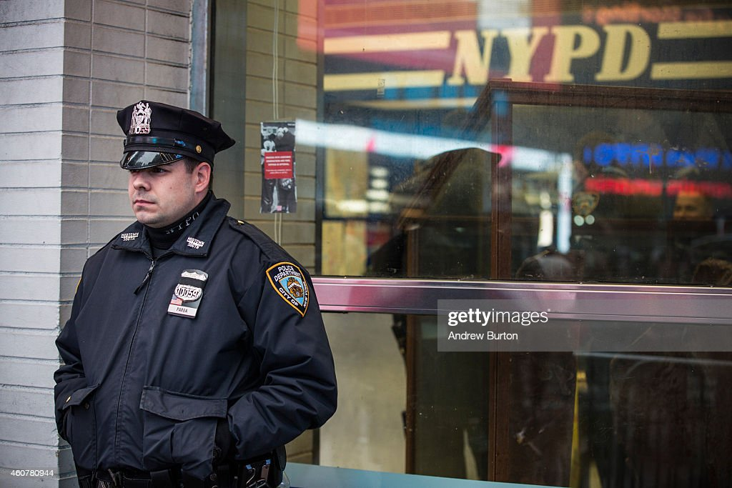 A police officer stands guard outside a New York Police Department substation in Times Square on December 22 2014 in New York City Police officers...