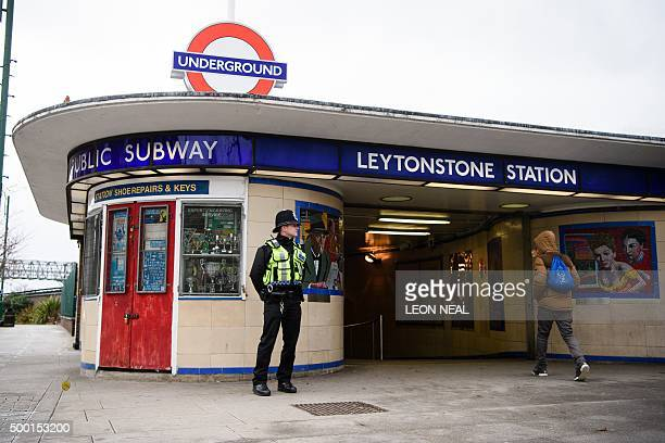 A police officer stands guard outside Leytonstone station in north London on December 6 a day after three people were stabbed in what police are...