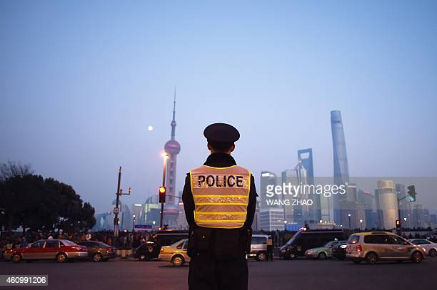 A police officer stands guard to maintain traffic safety at the site of the New Year's Eve stampede in Shanghai on January 3 2015 Dozens of deaths...