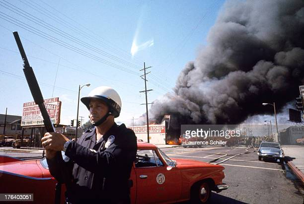 A police officer stands guard to secure a perimeter in the Watts neighborhood as members of the Los Angeles Fire Department battle a fire that...