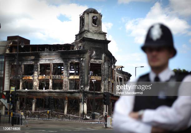 A police officer stands in front of a burnt out Carpetright shop in Tottenham on August 8 2011 in London England Pockets of rioting and looting took...