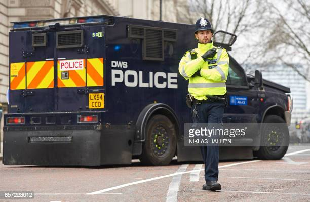 A police officer stands in front of an armoured police personnel carrier on a street leading to the Houses of Parliament in central London on March...