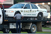 A police officer stands in front of an East Baton Rouge police car with bullet holes as it's towed away from the scene where three police officers...