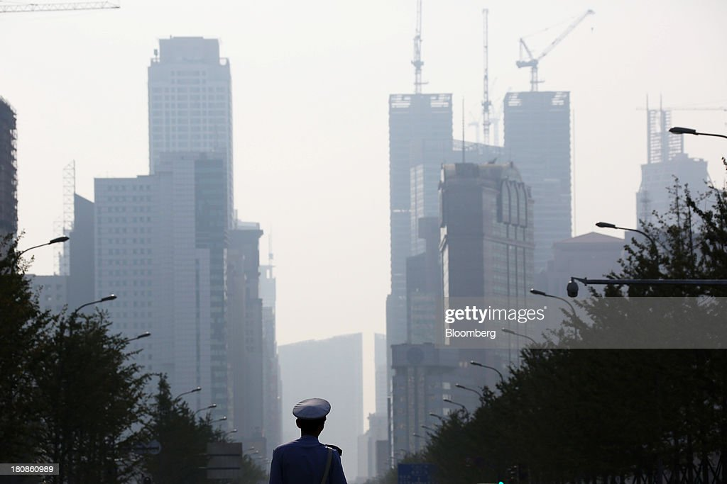 A police officer stands in front of buildings in Dalian, China, on Friday, Sept. 13, 2013. Goldman Sachs Group Inc. this month raised its estimate for China's economic growth for the third and fourth quarters, citing improving global demand and a stronger-than-expected domestic industrial recovery. Photographer: Tomohiro Ohsumi/Bloomberg via Getty Images