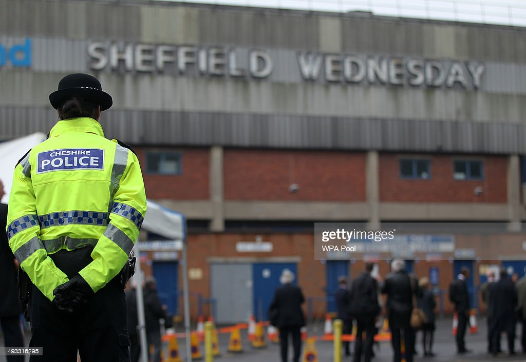 A police officer stands in front of members of the press outside the Hillsborough stadium in Sheffield as jurors on the inquest into the deaths of 96 Liverpool football fans killed in the Hillsborough disaster visit the stadium on May 23, 2014 in Hillsborough, England.
